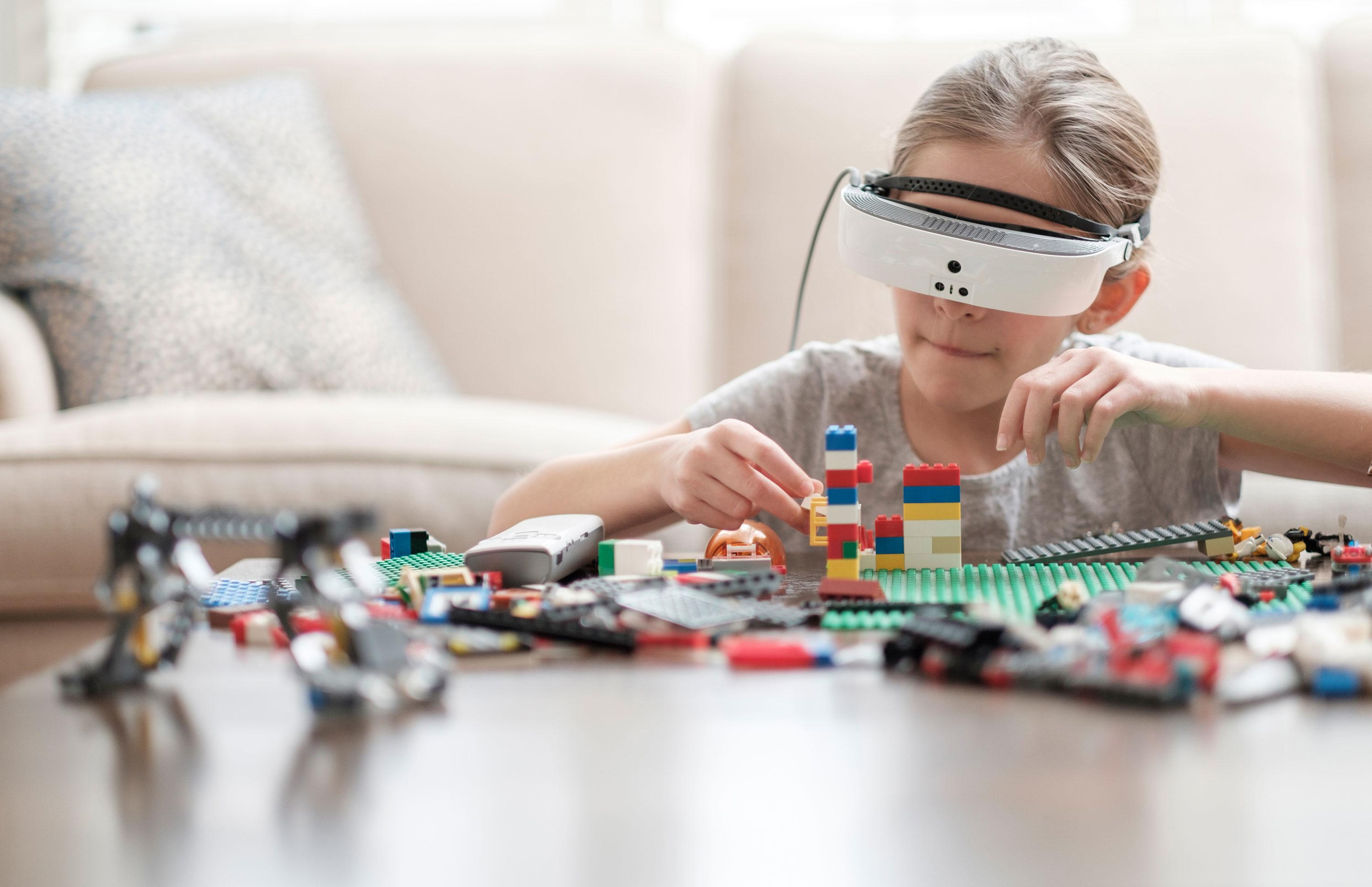 A child wearing eSight and using it to build Lego