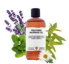 Brown plastic bottle and black cap with white label showing relaxing massage oil, white background with leafs and flowers