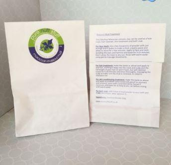 White paper bag with green and blue pure nuff stuff leaf logo on front showing moroccan rhassoul mud. Reverse of bag shown displaying usage instructions