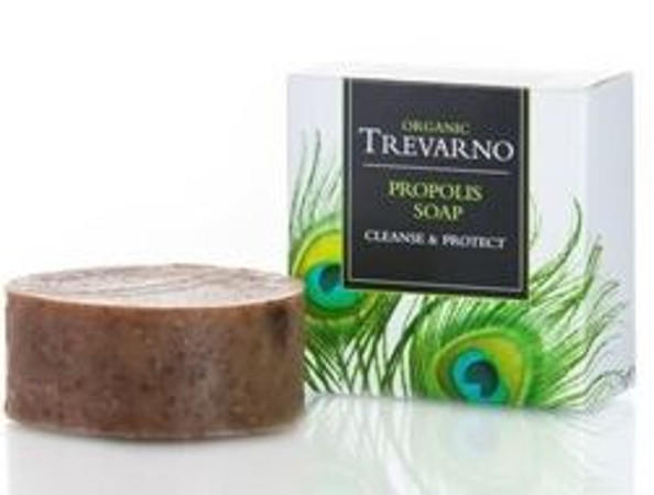 brown round soap, white square box with green feathers, green writing trevarno organic propolis soap