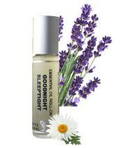 clear glass roller ball bottle with clear label showing goodnight roll on. Background of lavender and chamomile flowers