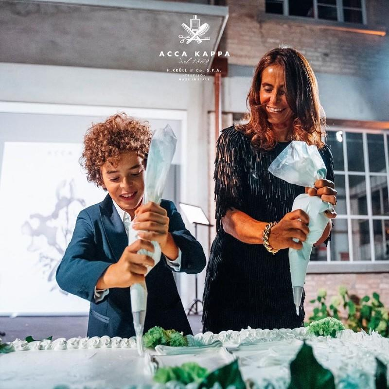 ACCA KAPPA MD, Elisa Gera, decorates the cake with her son to mark the occasion