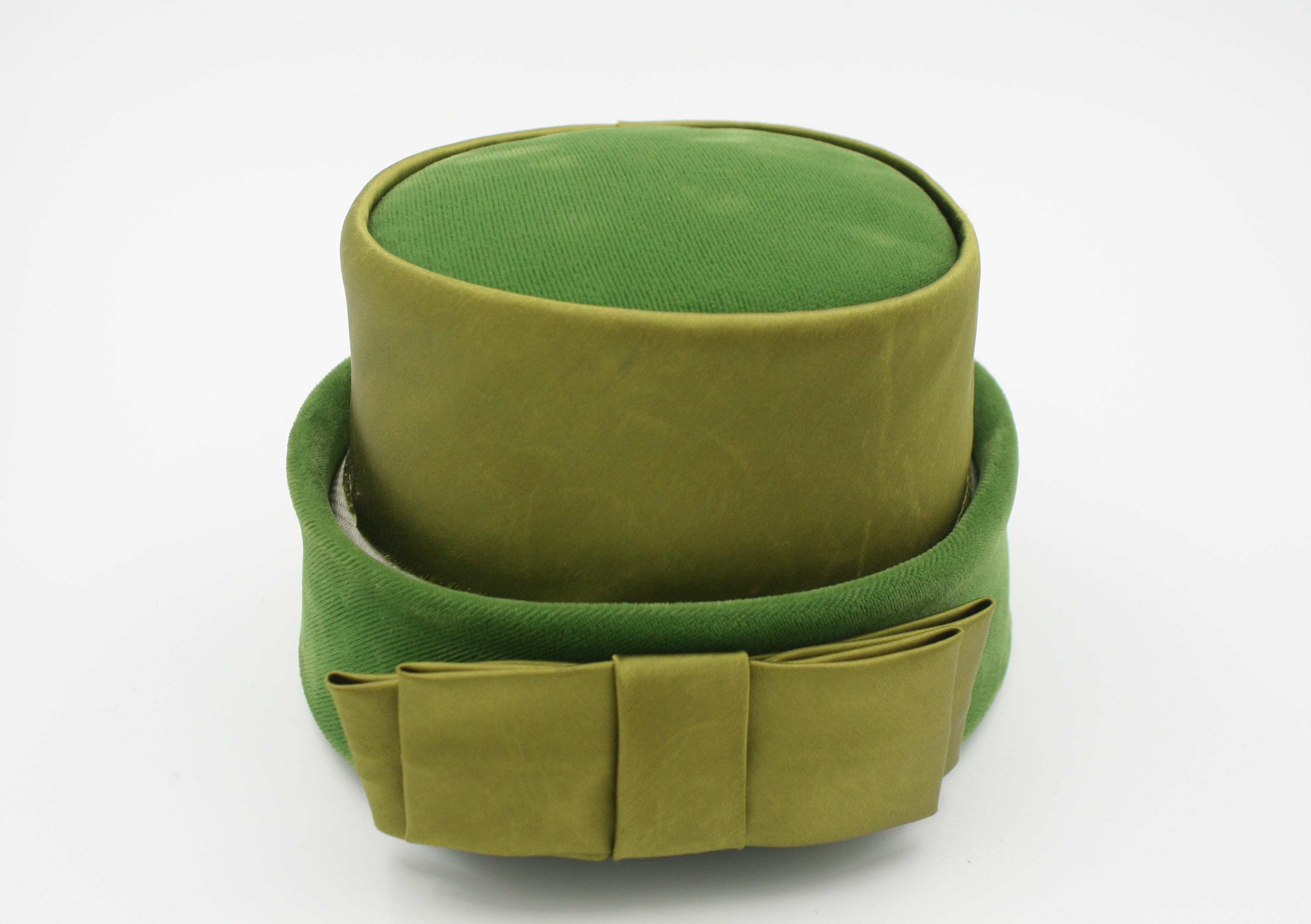 A green velvet and lime green satin hat from circa 1950's, this hat features a large lime green satin bow at the front. Lined in green satin.