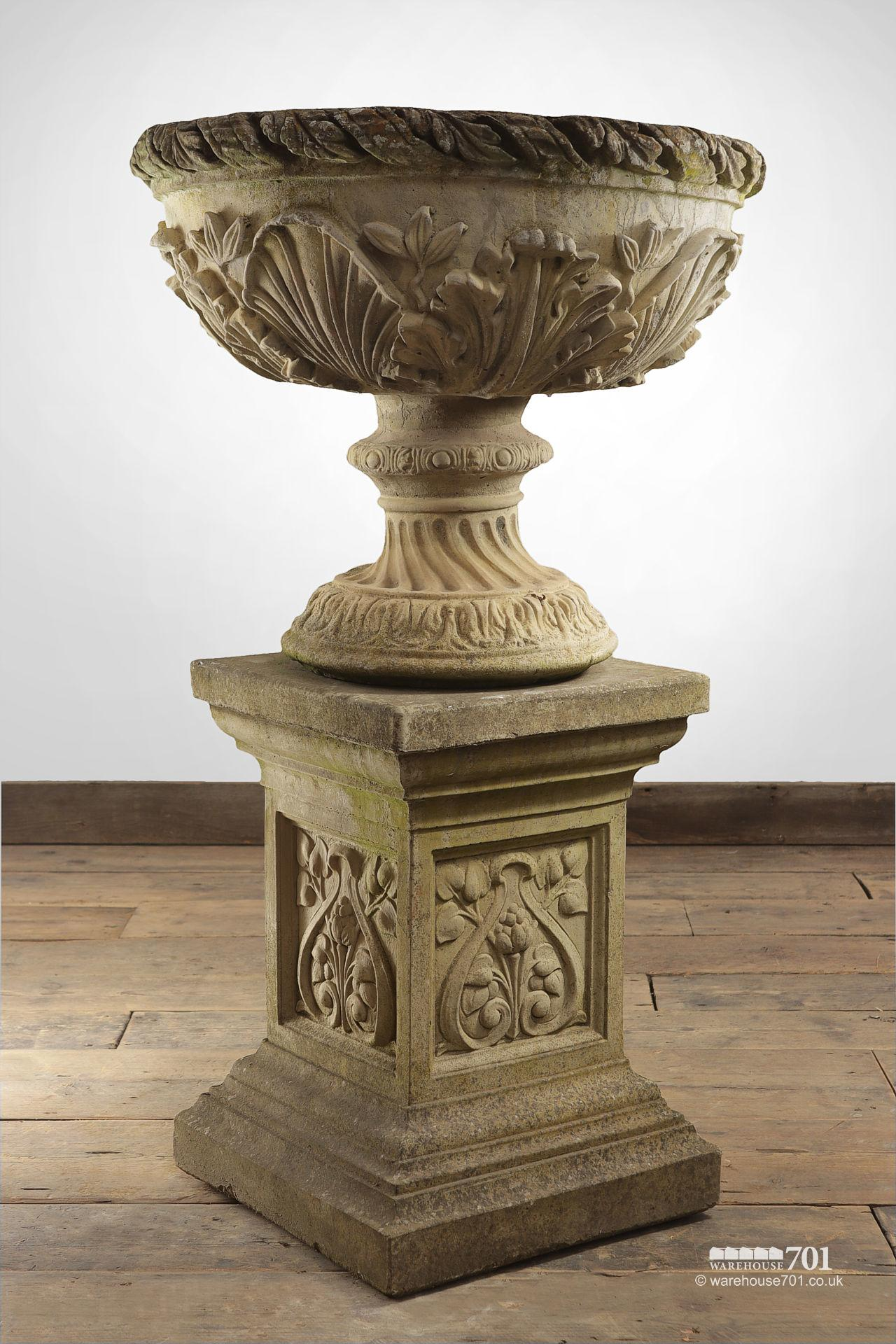 Pair of composite Floral Stone Urns on Plinths