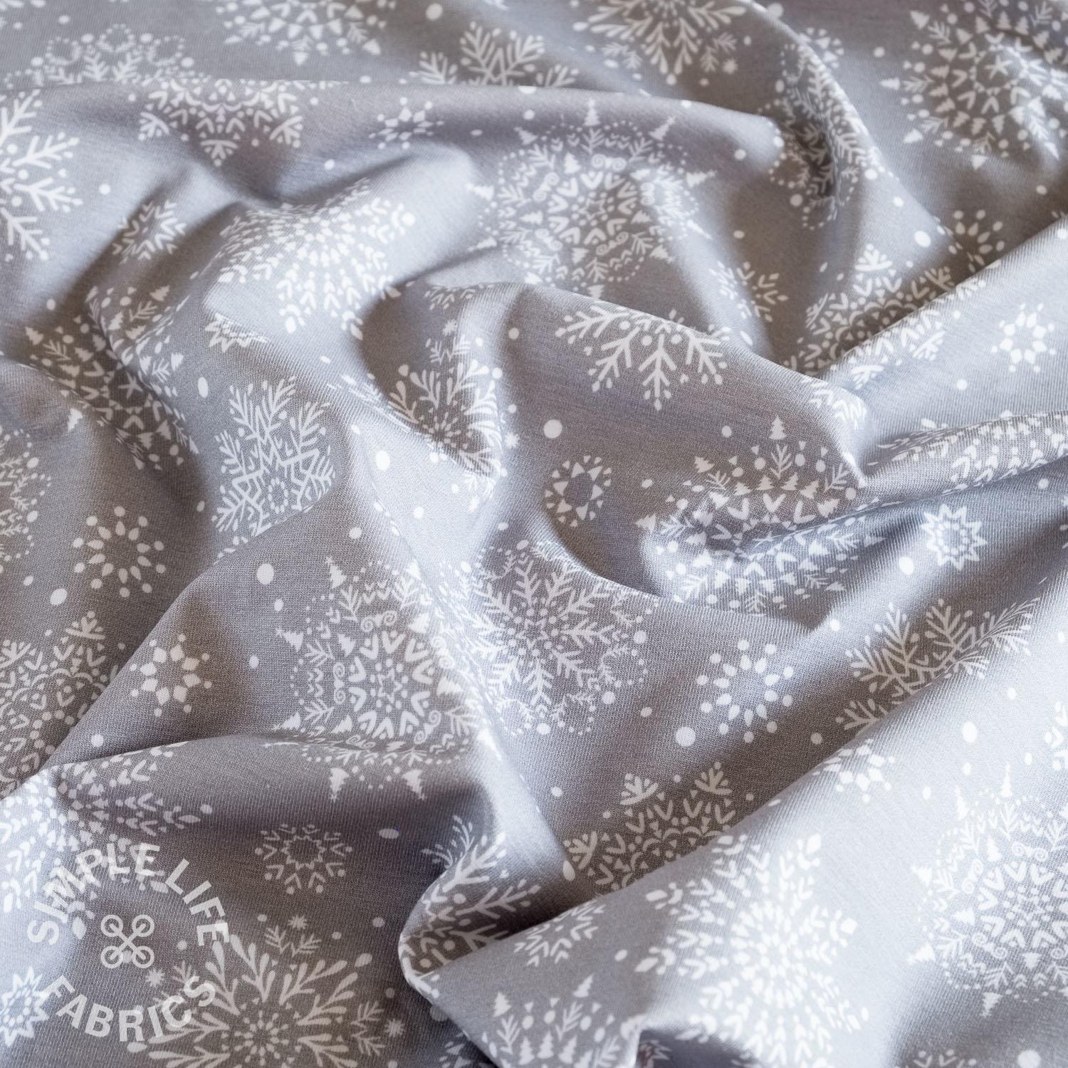 Snowflakes on grey Christmas jersey fabric