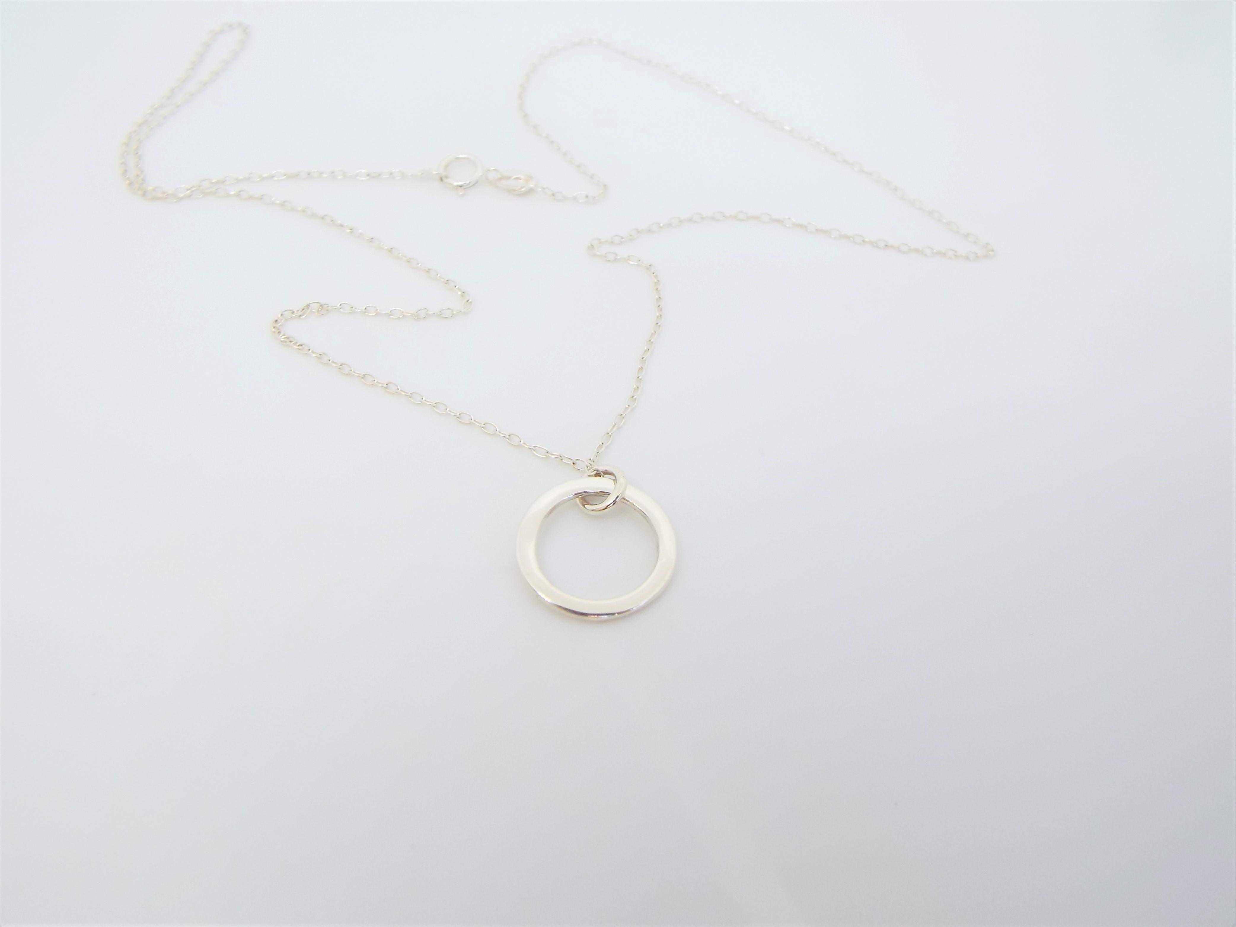 dainty silver circle pendant necklace on a chain
