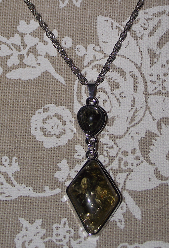 Black and gold pendant on a silver fashion chain,
