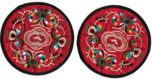 Small red Chinese table mats with embroidered oriental patterns,