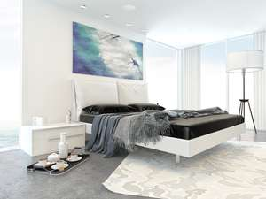 white bedroom with dark covers and installed ceiling speaker