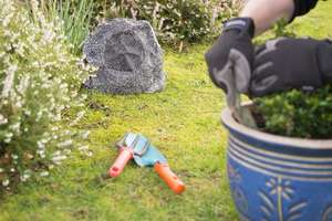 Lithe Audio Bluetooth Outdoor Garden Rock Speaker in garden with person potting a plant wearing gloves