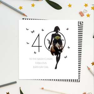A stunning, luxury, handcrafted card with gem embellishments and feathers from Five Dollar Shake. Showing A Woman In Black Silhouette Standing In Front Of The Number 40. Caption: 'To The Sassy, Classy, Fabulous Birthday Girl'. Blank Inside For Your Own Message. Complete With White Envelope With Black and White Striped Border.