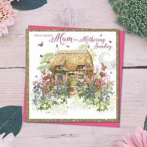 ' For A Lovely Mum On Mothering Sunday' Card Featuring A Beautiful thatched Cottage With Cottage Garden. Added Gold Sparkle Border and Bright Pink Envelope