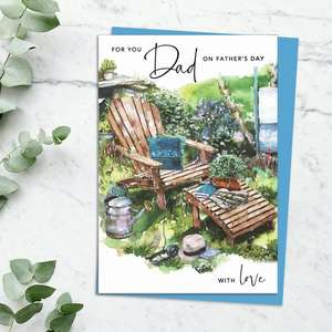 'For You Dad On Father's Day With Love' Card Featuring A Sun Lounger With Books And Watering Can, In The Garden. With Blue Foiled Lettering, Sparkle And Blue Envelope