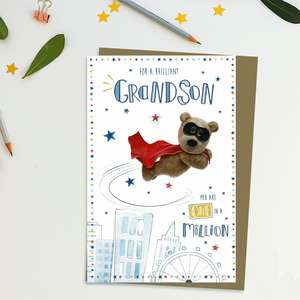 Superhero Barley Bear Grandson Birthday Card Alongside Its Kraft Envelope