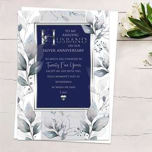 'To My Amazing Husband On Our Silver Anniversary' Card Showing A Border Of Leaves Around A Navy Rectangle With Gold Foiled Edge. Heartfelt Words And White Envelope