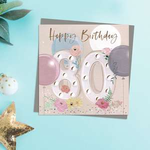 Happy 80th Birthday Design Featuring Embellished Flowers And Balloons. Completed With Gold Foil lettering And A Co-Ordinating Grey Envelope