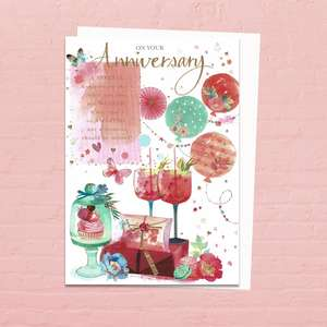 'On Your Anniversary' Card Featuring Vibrant Images Of Cocktails, Balloons And Gifts. With Added Gold Foil Detail And White Envelope