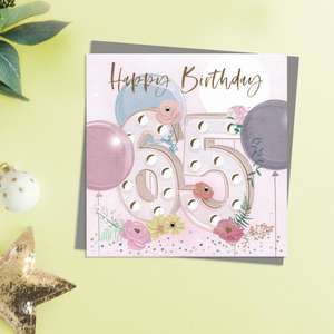 Happy 65th Birthday Design Featuring Embellished Flowers and Balloons. Completed With Gold Foil Lettering and A Co-Ordinating Envelope