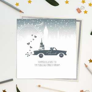 Stunning, Luxury, Handcrafted Wedding Day Design From Five Dollar Shake. Image Shows A Black Car In Silhouette Full Of Gifts With A Skyline In The Background. On The Side Of The Car Is Written-Just Married. Caption: Congratulations To The Fabulous Bride And Groom. With Jewel Embellishments And Biodegradable Glitter Accents. Blank Inside For Own Message. Warm White Envelope With Silver Border.