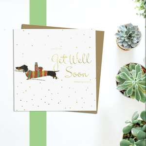 Get Well Soon Sausage Dog Greeting Card Alongside Its Kraft Envelope