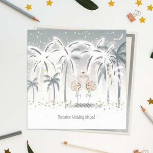 A Stunning, Luxury, Handcrafted Wedding Day Card In Soft Grey With Pink Showing Sparkling Palm Trees And Two Jewelled Flamingos On The Beach. Caption: Romantic Wedding Abroad. With Biodegradable Glitter And Compostable Wrap. Blank Inside For Own Message. Warm White Envelope With Silver Border.