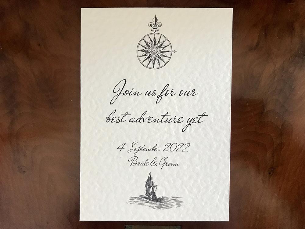 Ivory wedding invitation with compass and ship