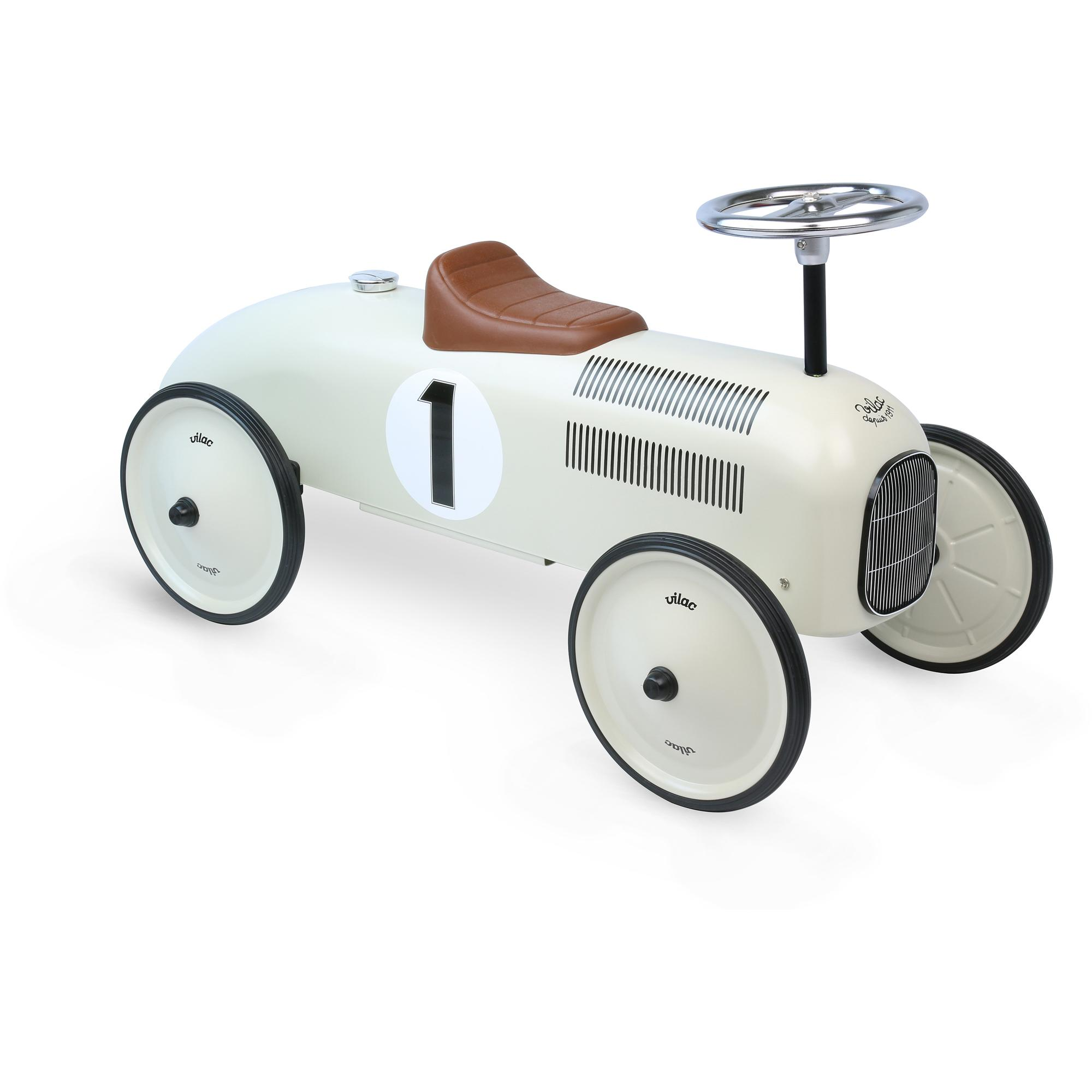 Off-white metal Vilac ride-on car with brown leatherette seat.