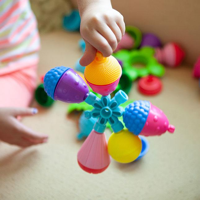 Child's hands holding large colourful play beads joined together.