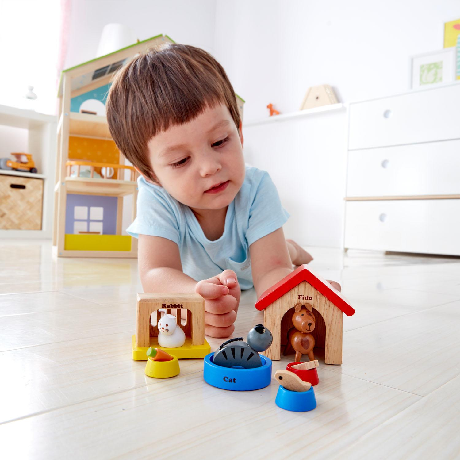 Child lying on the floor in a light coloured bedroom playing with the dolls house pets.