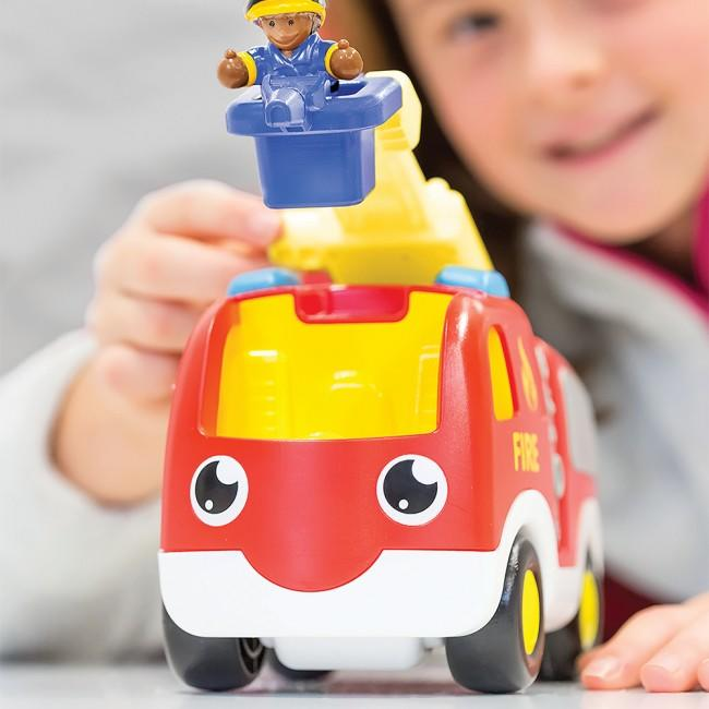 Young child playing with fire truck set.