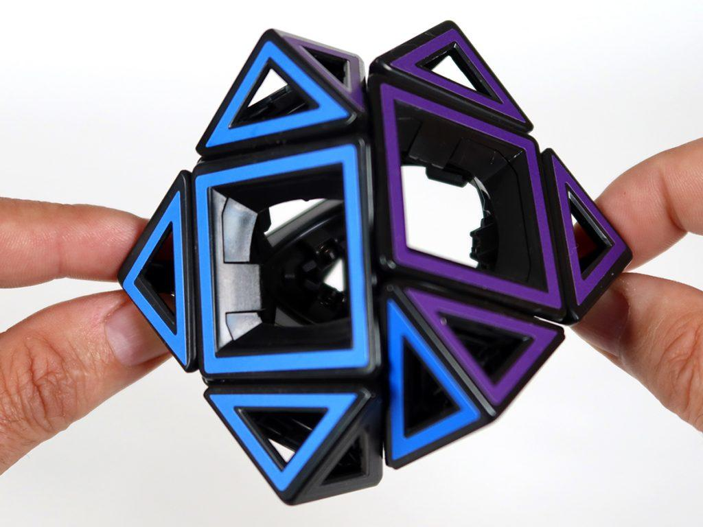 Pair of hands twisting the Hollow Skewb puzzle.