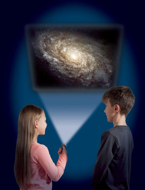Girl and boy using the torch to project an image of the milky way onto a wall.