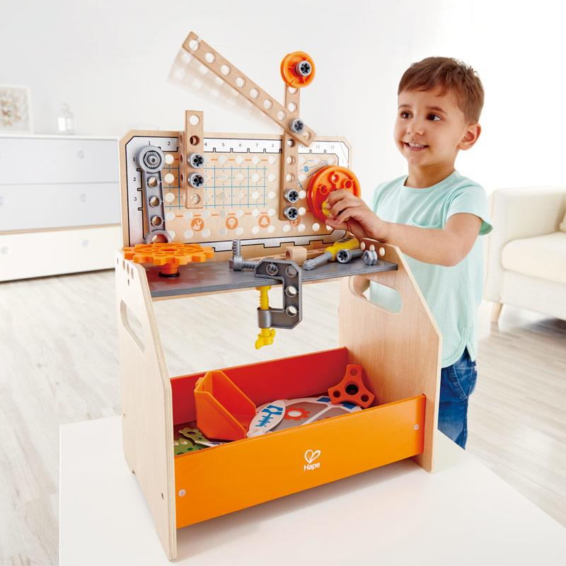 Boy standing up and playing with the inventor workbench on a table in front of him.