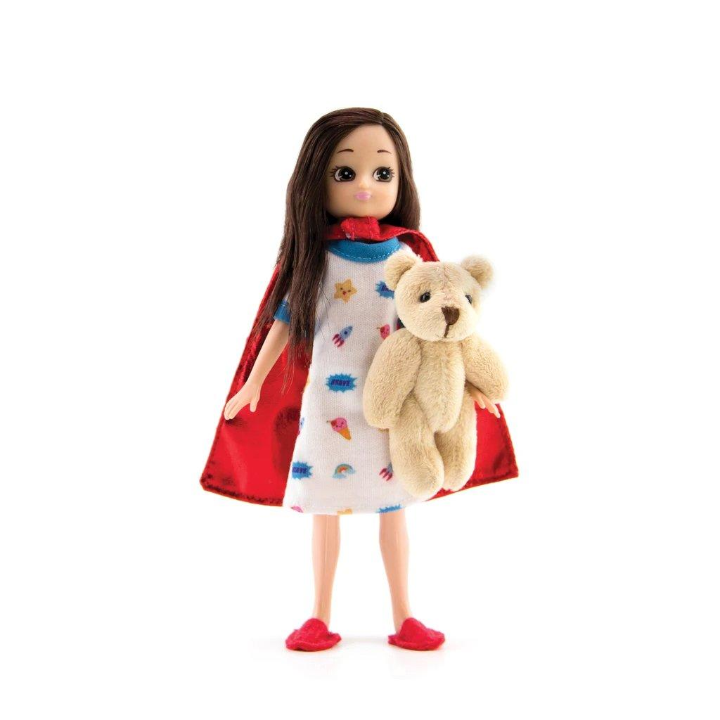 Lottie Hospital Doll in nightgown and cape holding a fluffy teddy.