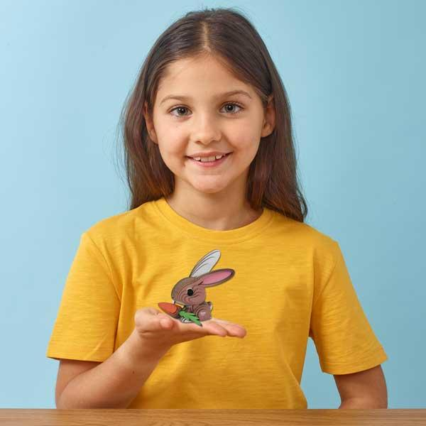 Girl in a yellow tshirt holding the Eugy rabbit model on the palm of her hand. Light blue background.