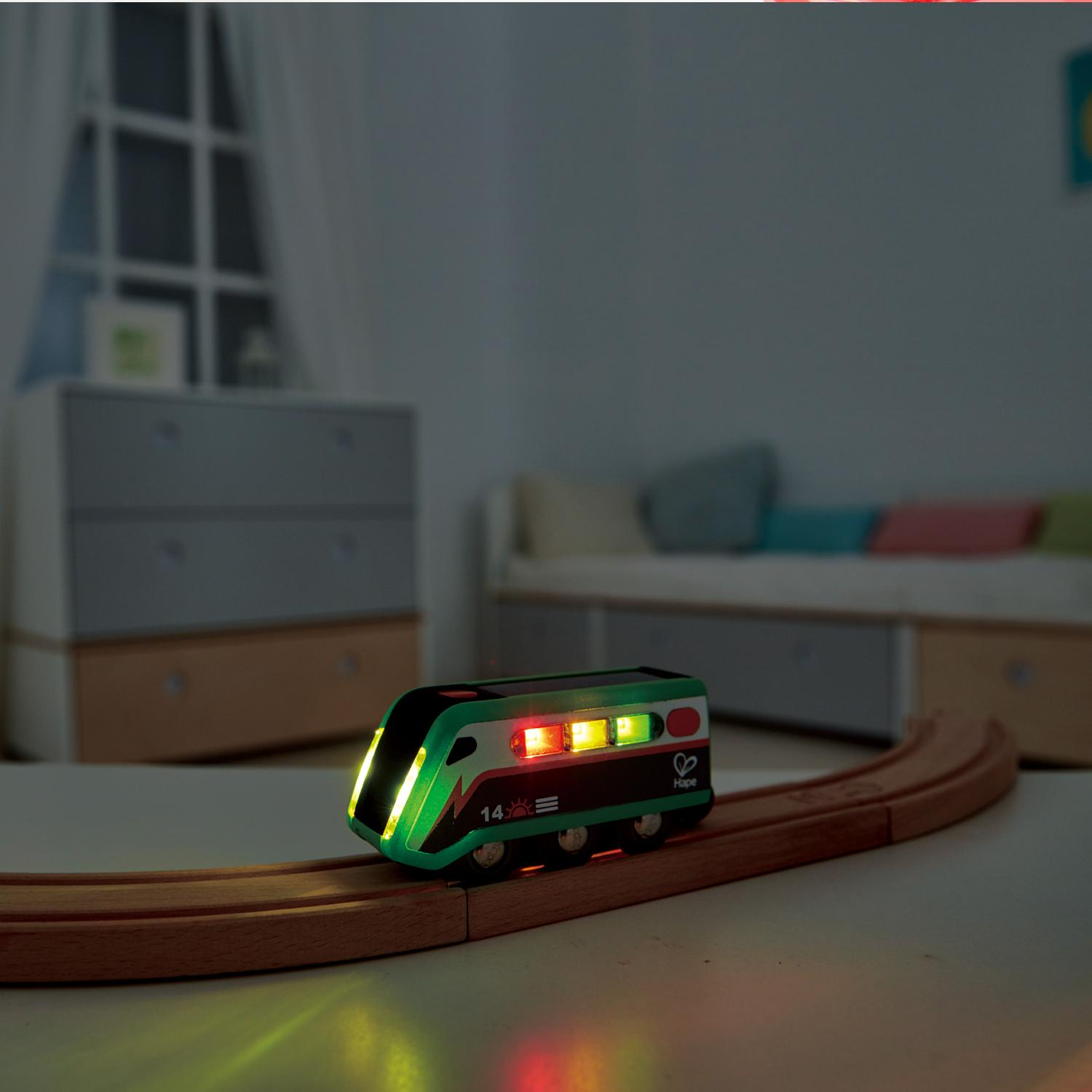 Solar-powered engine with lights on going round on a train track in a dimmed room.
