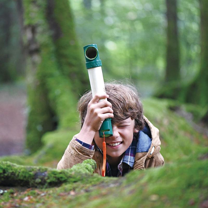 Boy in a forest peering from behind a log with his periscope.