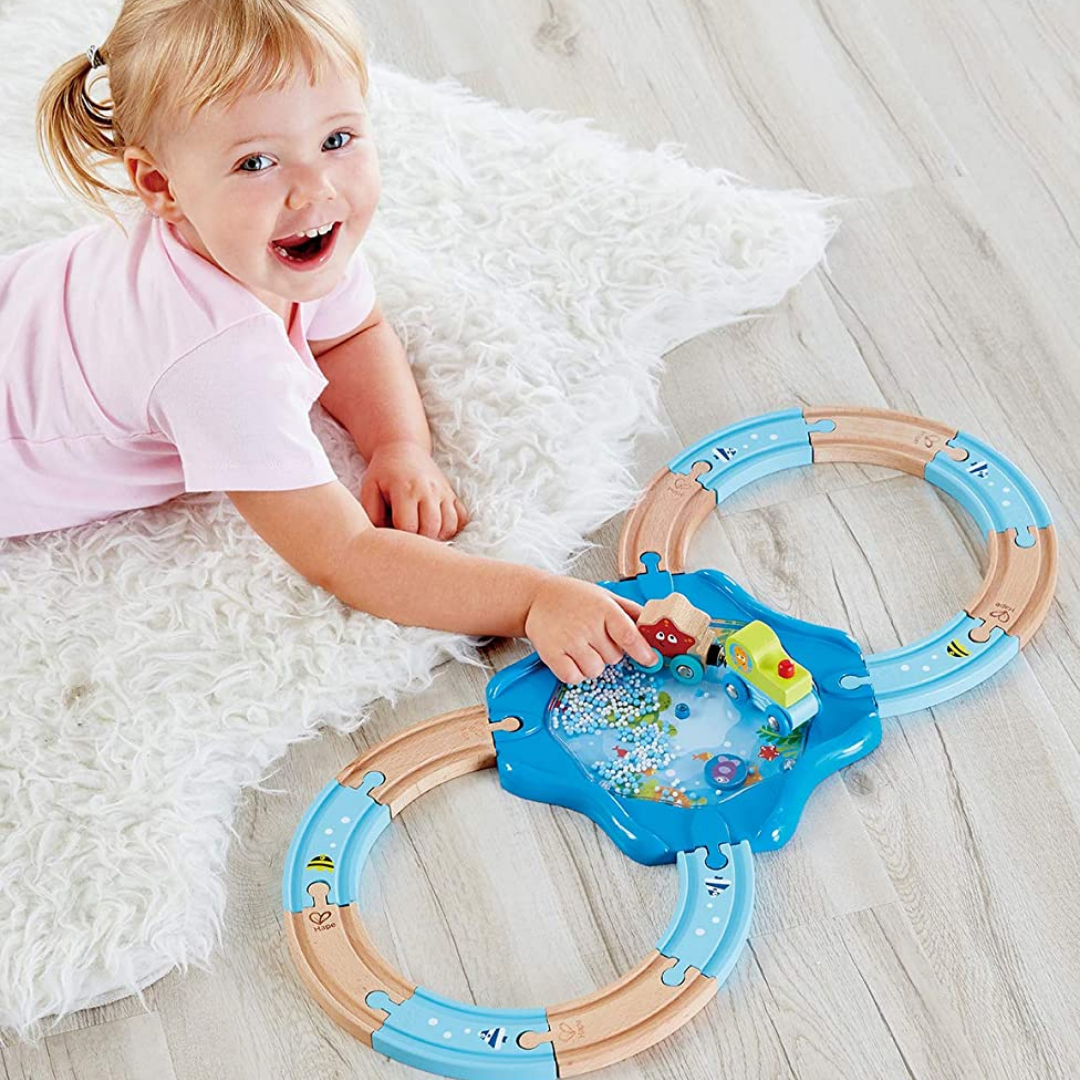 Girl lying on a rug playing with figure-of-8 train track with a pretend pool in the middle.