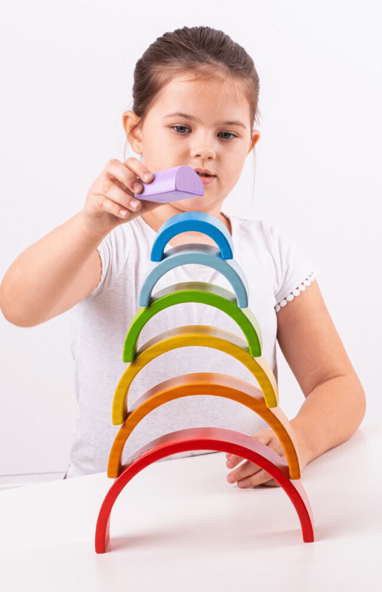 Girl stacking rainbow arches.