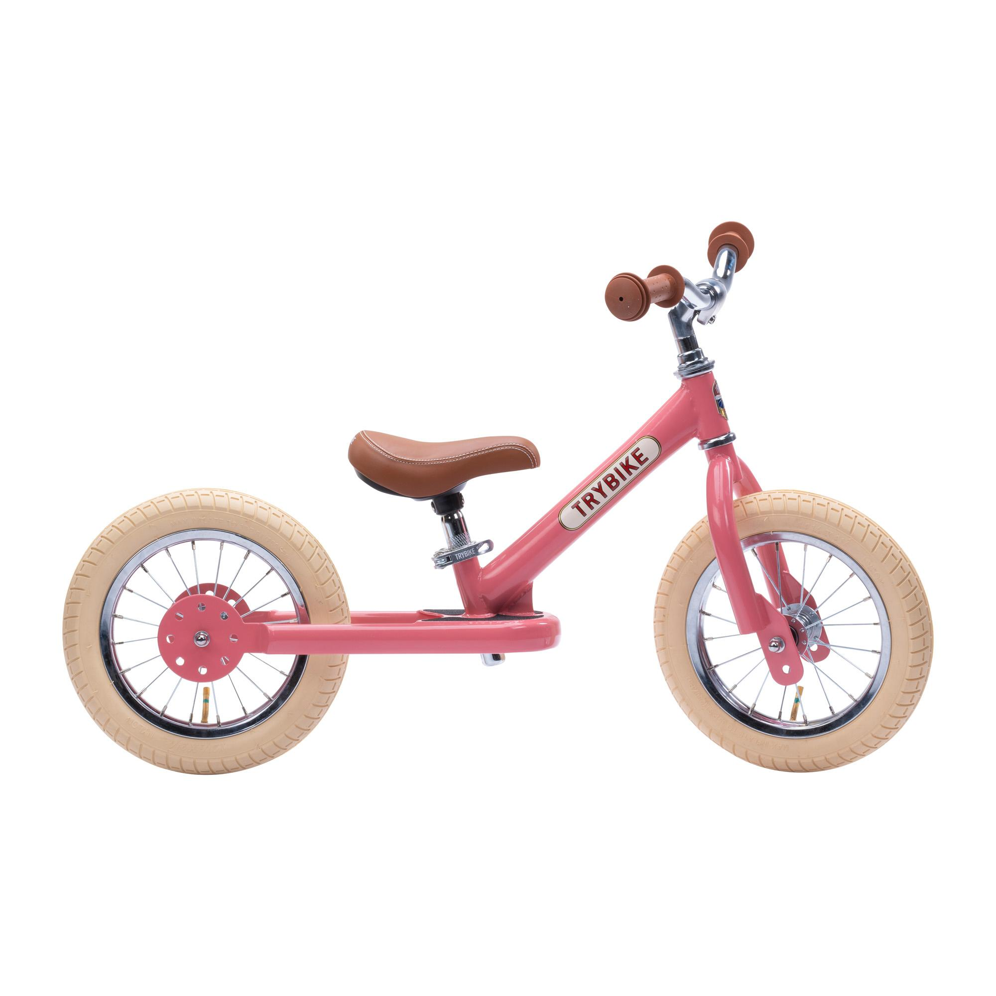 Side view of pink Trybike on white background.
