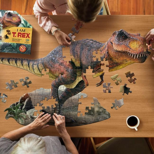 Image from above of people placing pieces of the large T Rex jigsaw.