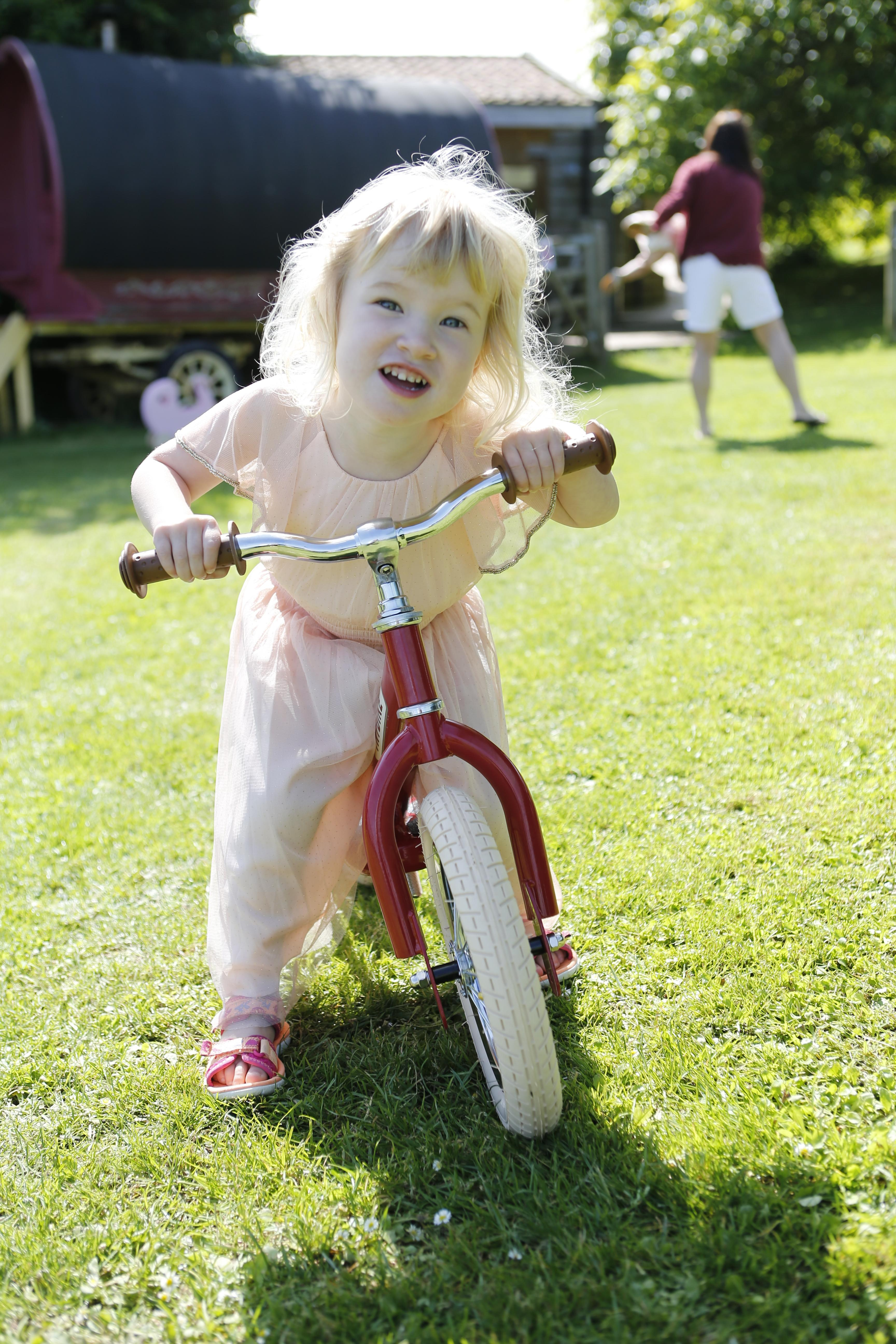 Little girl in a dress riding a red Trybike balance bike.