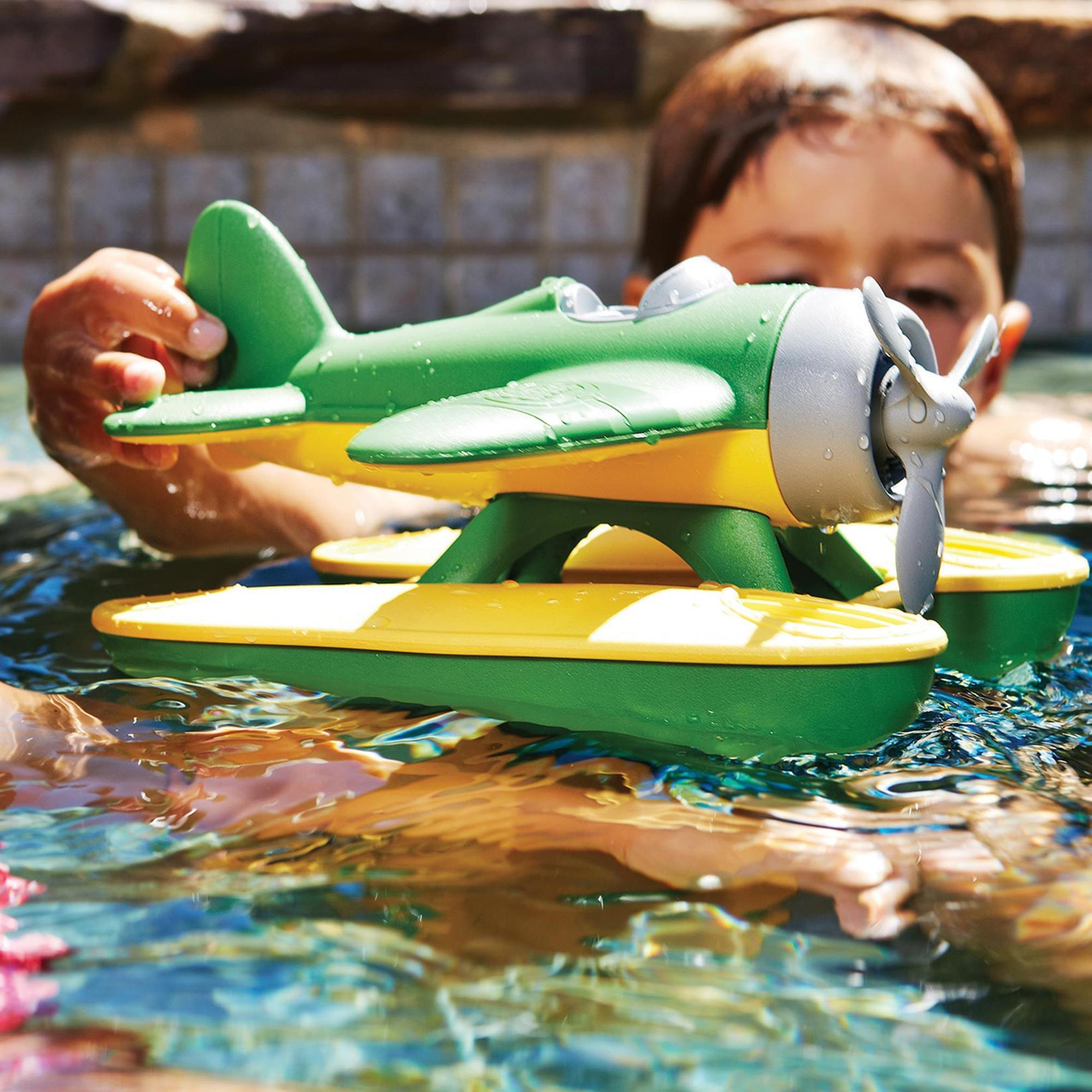 Boy playing with green and yellow seaplane as it floats on water.