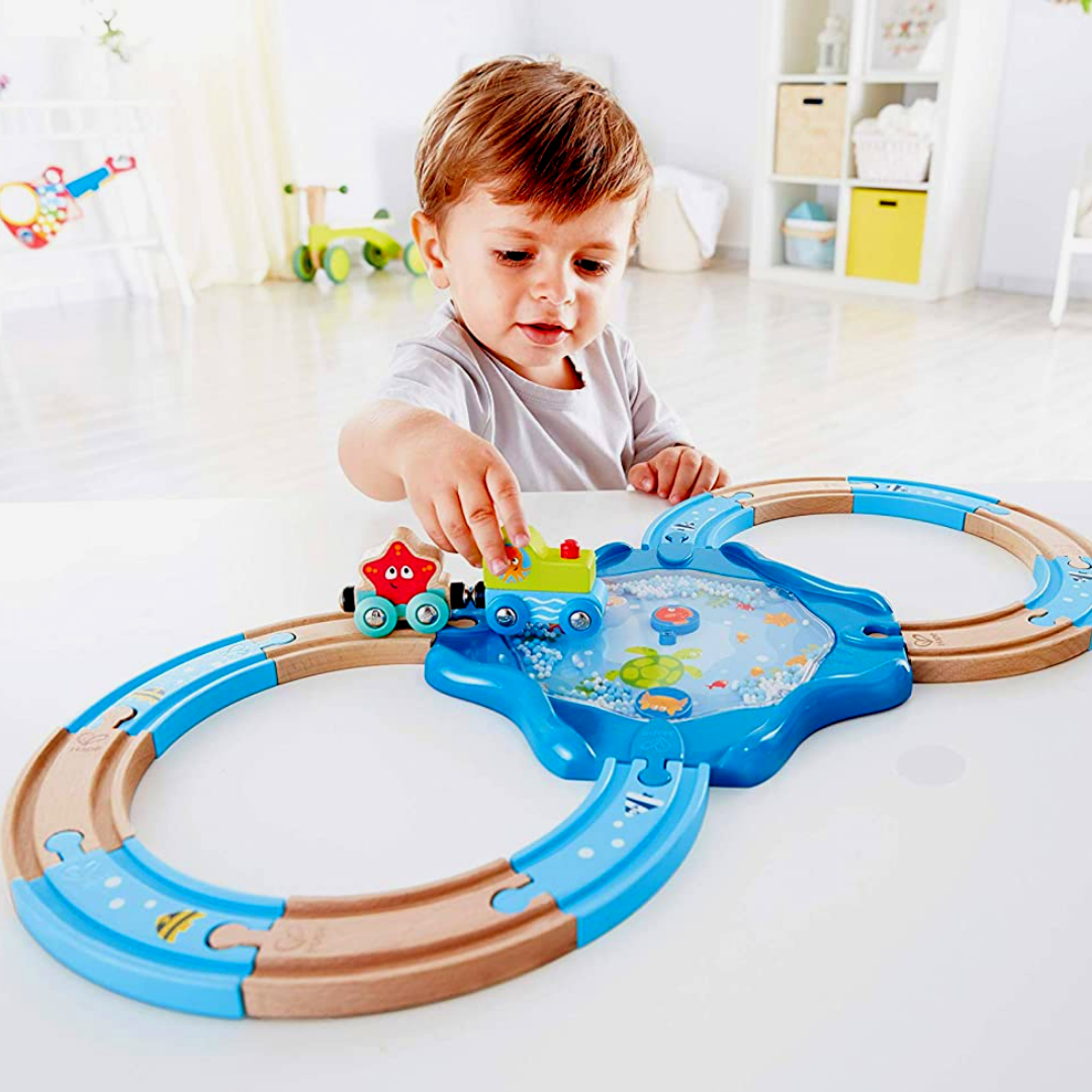 Little boy playing with under-sea themed figure of 8 rail track.