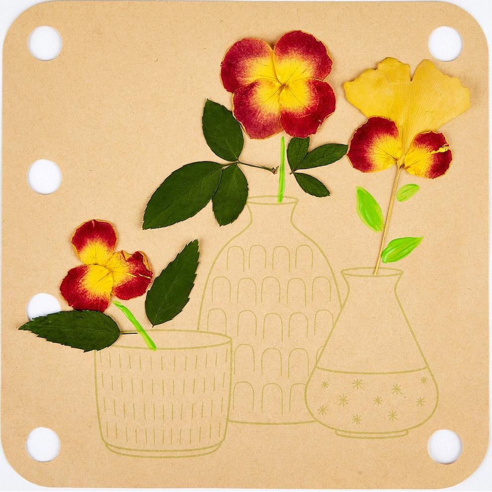 Flower press plate with stencil for placing petals and decorating with paint.