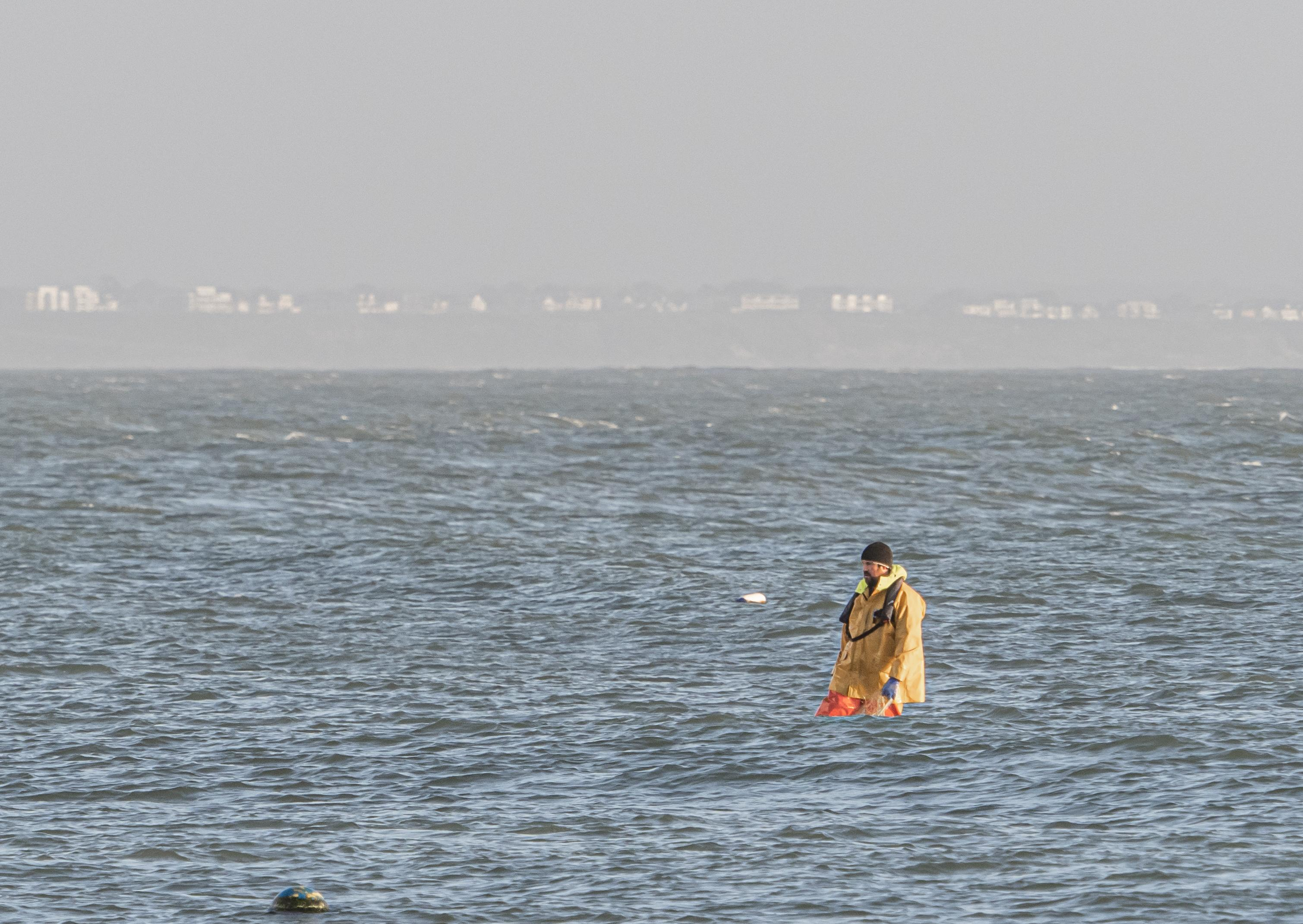 Here's an image using the rule of thirds - the fisherman is in a boat obscured by the swell!