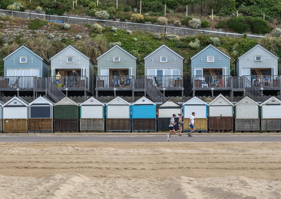 A image called Three Runners and Beach Huts, taken at Boscombe in Bournemouth in June 2021.