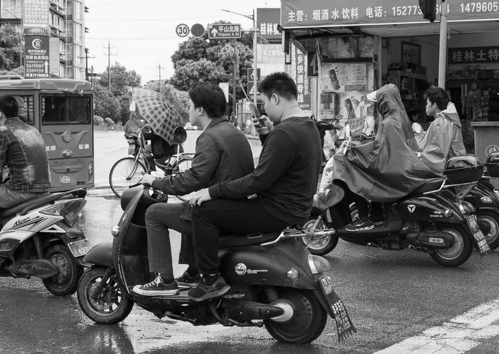 Rear Messenger - a black and white print of two moped riders in Guilin China