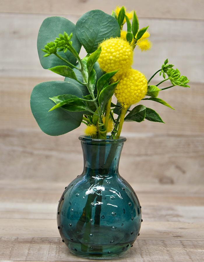 SMALL GREEN GLASS VASE WITH YELLOW ARTIFICIAL FLOWER ARRANGEMENT