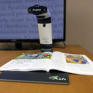 A mid range photo of the Prisma. A magazine is placed under the device and magnified on the screen in the background.